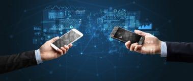 Deux mains tenant des smartphones sur des données commerciales de synchronisation photographie stock