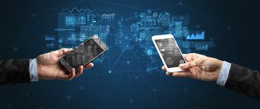 Deux mains tenant des smartphones sur des données commerciales de synchronisation photo stock