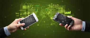 Deux mains tenant des smartphones sur des données commerciales de synchronisation photos stock