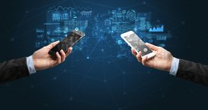 Deux mains tenant des smartphones sur des donn?es commerciales de synchronisation images stock