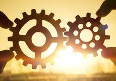Deux mains tenant des vitesses ensemble Contre le coucher du soleil Photo stock