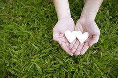 Deux mains tenant deux coeurs blancs sur l'herbe verte Photo stock