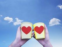 Deux mains tenant les tasses de café de papier jaunes avec le sha rouge de coeur Photographie stock libre de droits