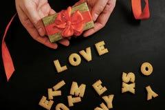 Deux mains tenant un cadeau avec le ruban rouge avec amour de mot Images stock