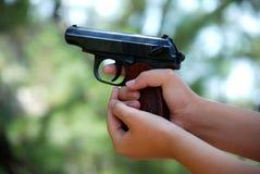 Deux mains tenant une arme à feu Images stock