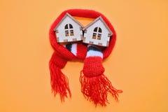 Deux maisons en bois de jouet avec des fenêtres dans une écharpe rouge sur un fond orange, maison chaude, isolation des maisons,  photographie stock libre de droits