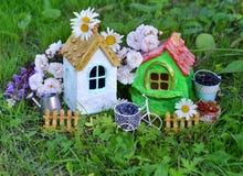 Deux maisons mignonnes avec la baie d'été, la boîte d'arrosage et les fleurs dans le jardin Photo stock