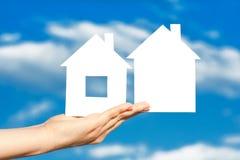 Deux maisons sur la main sur le ciel bleu Image stock