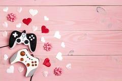 Deux manettes avec des coeurs et espace de copie sur le fond en bois rose Concept de jeu de vacances Concept de jour de valentine photographie stock