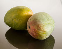 Deux mangues sur la surface se reflétante Photos stock