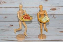 Deux mannequins en bois servant des panneaux de fromage Images stock