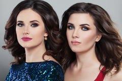 Deux mannequins fascinants de femmes coiffure et maquillage de soirée Image libre de droits