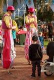 Deux marcheurs d'échasse amusant des enfants photo stock