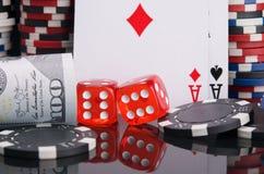 Deux matrices rouges, entourées par un ensemble de jeu de dollars, cartes, puces de casino, sur un fond noir photographie stock