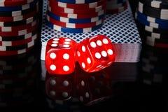 Deux matrices rouges, une plate-forme des cartes et jetons de poker, sur un fond noir avec des tracés Photos stock