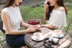 Deux medias sociaux de belle utilisation indépendante de femme sur le smartphone dedans Image stock