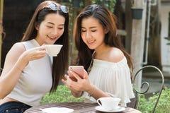 Deux medias sociaux de belle utilisation indépendante de femme sur le smartphone dedans Photographie stock