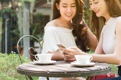 Deux medias sociaux de belle utilisation indépendante de femme sur le smartphone dedans Photos stock