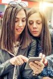 Deux medias sociaux de observation heureux d'Internet d'amie dans le smartph Photographie stock libre de droits