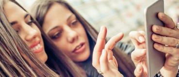 Deux medias sociaux de observation heureux d'Internet d'amie dans le smartph Photographie stock