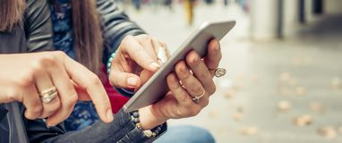 Deux medias sociaux de observation heureux d'Internet d'amie dans le smartph Images libres de droits