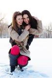 Deux meilleurs amis étreignant dans la neige Photographie stock