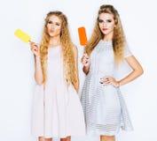 Deux meilleurs amis ayant la crème glacée ensemble d'intérieur sur le fond jaune Fermez-vous des jeunes femmes mangeant la crème  Images stock