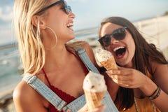 Deux meilleurs amis ayant la crème glacée ensemble dehors Photos libres de droits