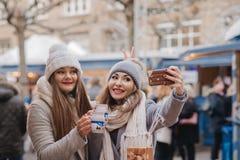 Deux meilleurs amis de filles boivent du vin chaud et font une photo d'individu dessus Images stock