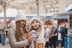 Deux meilleurs amis de filles boivent du vin chaud et font une photo d'individu dessus Photo libre de droits