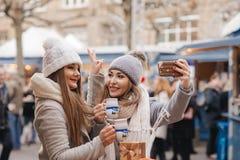 Deux meilleurs amis de filles boivent du vin chaud et font une photo d'individu dessus Images libres de droits
