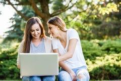 Deux meilleurs amis en parc, souriant et travaillant sur l'ordinateur portable Image stock