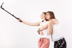 Deux meilleurs amis féminins ayant beaucoup d'amusement tout en prenant un selfie avec un bâton de selfie Images stock