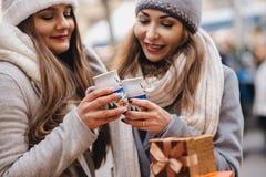 Deux meilleurs amis féminins buvant du vin chaud sur le deco c de Noël Image libre de droits