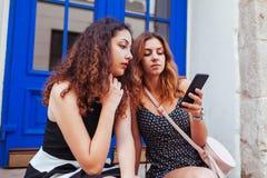 Deux meilleurs amis féminins causant tout en à l'aide du smartphone dans la ville Filles heureuses parlant et riant Photographie stock libre de droits