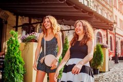 Deux meilleurs amis féminins se sont réunis par le café dans la ville Filles riant et ayant l'amusement dehors Photos stock