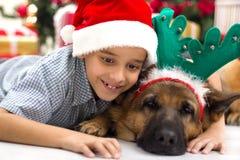 Deux meilleurs amis garçon et chien dans la célébration de nuit de Noël Photos stock