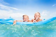 Deux meilleurs amis nageant sur des matrass et l'éclaboussement Photo libre de droits