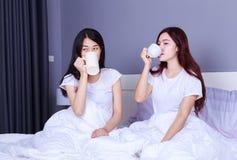 Deux meilleurs amis parlant et buvant une tasse de café sur le lit dedans Photographie stock libre de droits