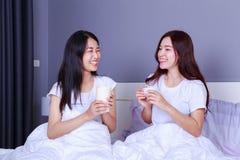 Deux meilleurs amis parlant et buvant une tasse de café sur le lit dedans Image stock