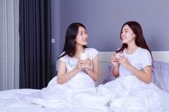 Deux meilleurs amis parlant et buvant une tasse de café sur le lit dedans Photo stock