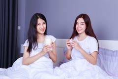 Deux meilleurs amis parlant et buvant une tasse de café sur le lit dedans Photo libre de droits