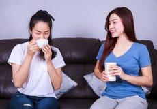 Deux meilleurs amis parlant et buvant une tasse de café sur le sofa dedans Photos stock