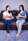Deux meilleurs amis parlant et buvant une tasse de café sur le sofa dedans Photo libre de droits