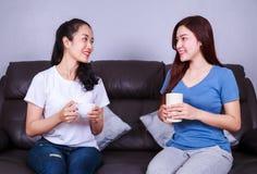 Deux meilleurs amis parlant et buvant une tasse de café sur le sofa dedans Photo stock