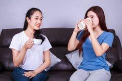 Deux meilleurs amis parlant et buvant une tasse de café sur le sofa dedans Image stock