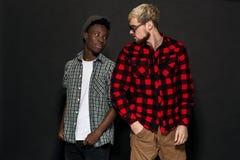 Deux meilleurs amis posent et ont l'amusement dans le studio Habillé dans des vêtements sport, chemises dans une cage Images libres de droits