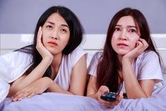 Deux meilleurs amis regardant la TV avec l'extérieur sur le lit dans la chambre à coucher Images libres de droits