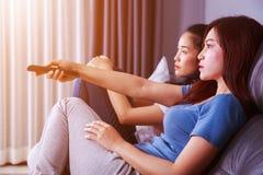 Deux meilleurs amis regardant la TV avec l'extérieur sur le sofa à la maison Photographie stock