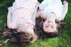 Deux meilleurs amis s'étendant ensemble sur la pelouse Photo libre de droits